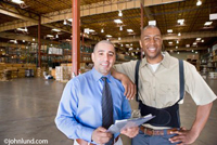A warehouse employee and his supervisor are standing together posing for this portrait.  The worker is resting his elbow on his bosses shoulder and smiling at the camera.